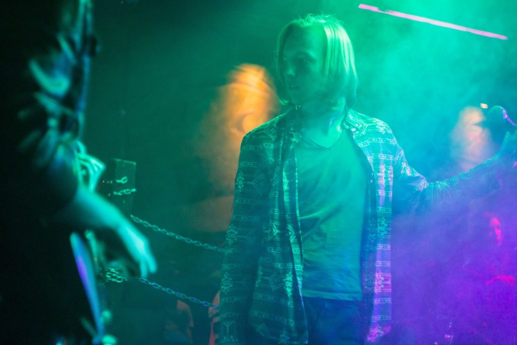 A performer pauses at a grunge rock concert.