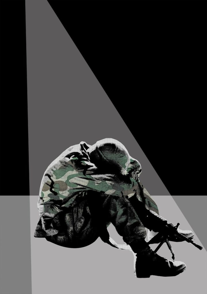 A seated soldier presses his face to his knees in despair.