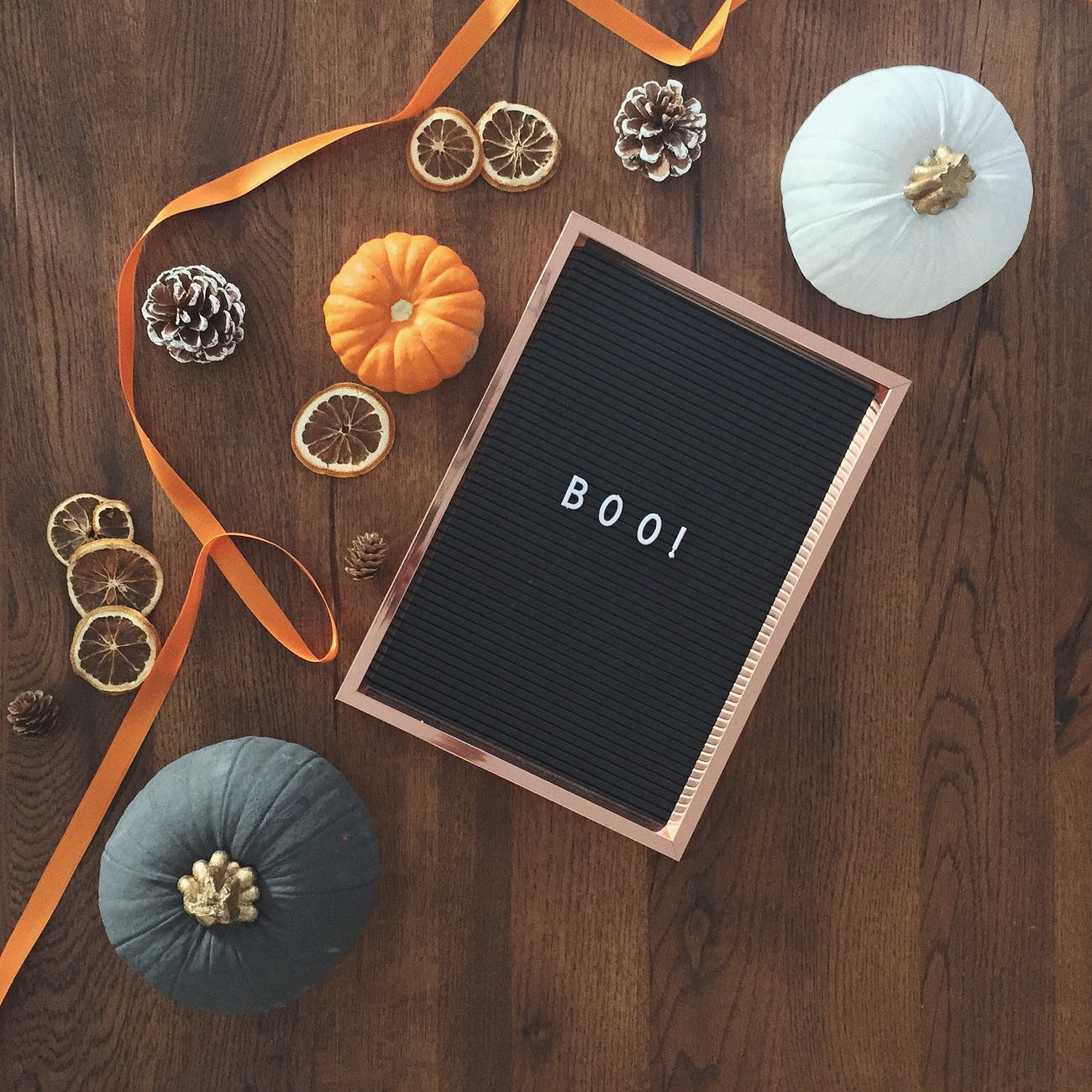 "Three gourds sitting near a black box with the word ""boo"" is evocative of the fall."