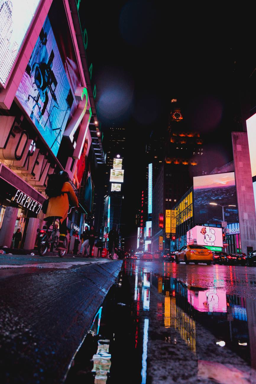 A New York City street near Times Square lit up in neon during the night.