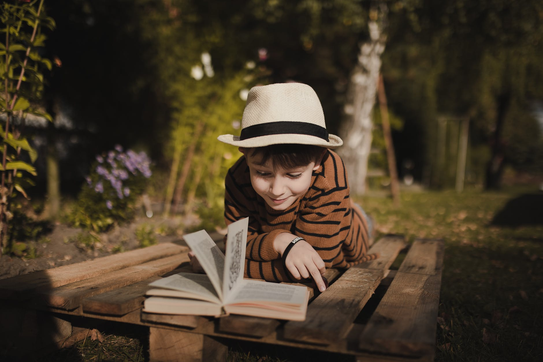 smiling boy reading book on bench in park