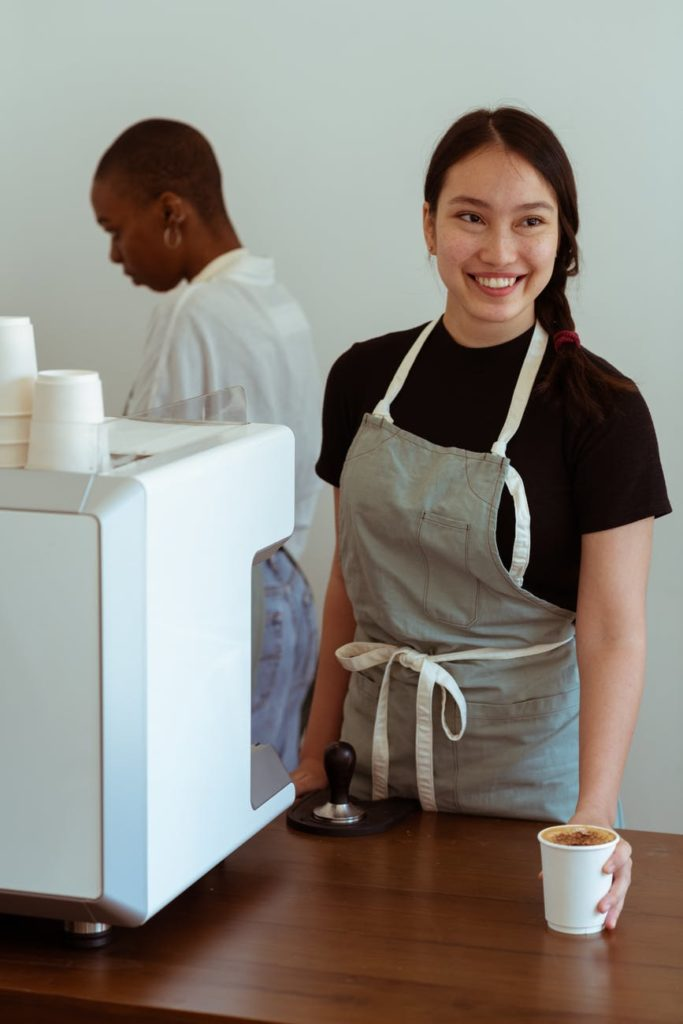 A woman at a coffee shop smiles as she serves coffee, but is she really happy with her work?
